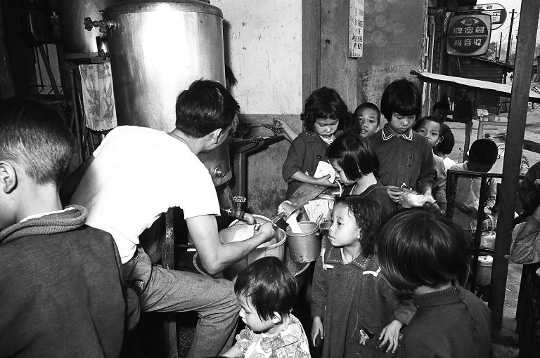 臺北基督教醫學協會環河南街醫療服務站,此為糧食和平援助計畫中的美援牛奶站。圖中的工作人員拿著杓子舀牛奶,許多兒童帶著水壺、鍋子排隊等著領取。(另開新視窗)