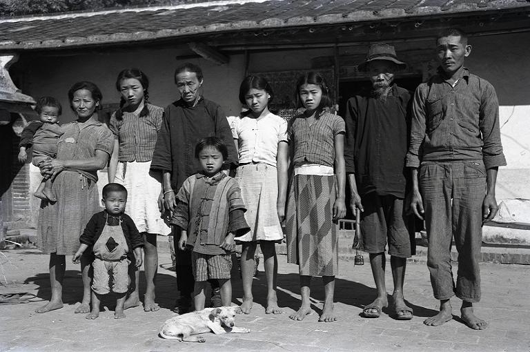 這張全家福照片,一家十口,外加一條狗,全數入鏡,可以看到當時從幼兒到老人的穿著打扮。鏡頭中,除了爺爺、奶奶穿著傳統的臺灣衫和鞋子以外,其餘的人都打著赤腳。(另開新視窗)