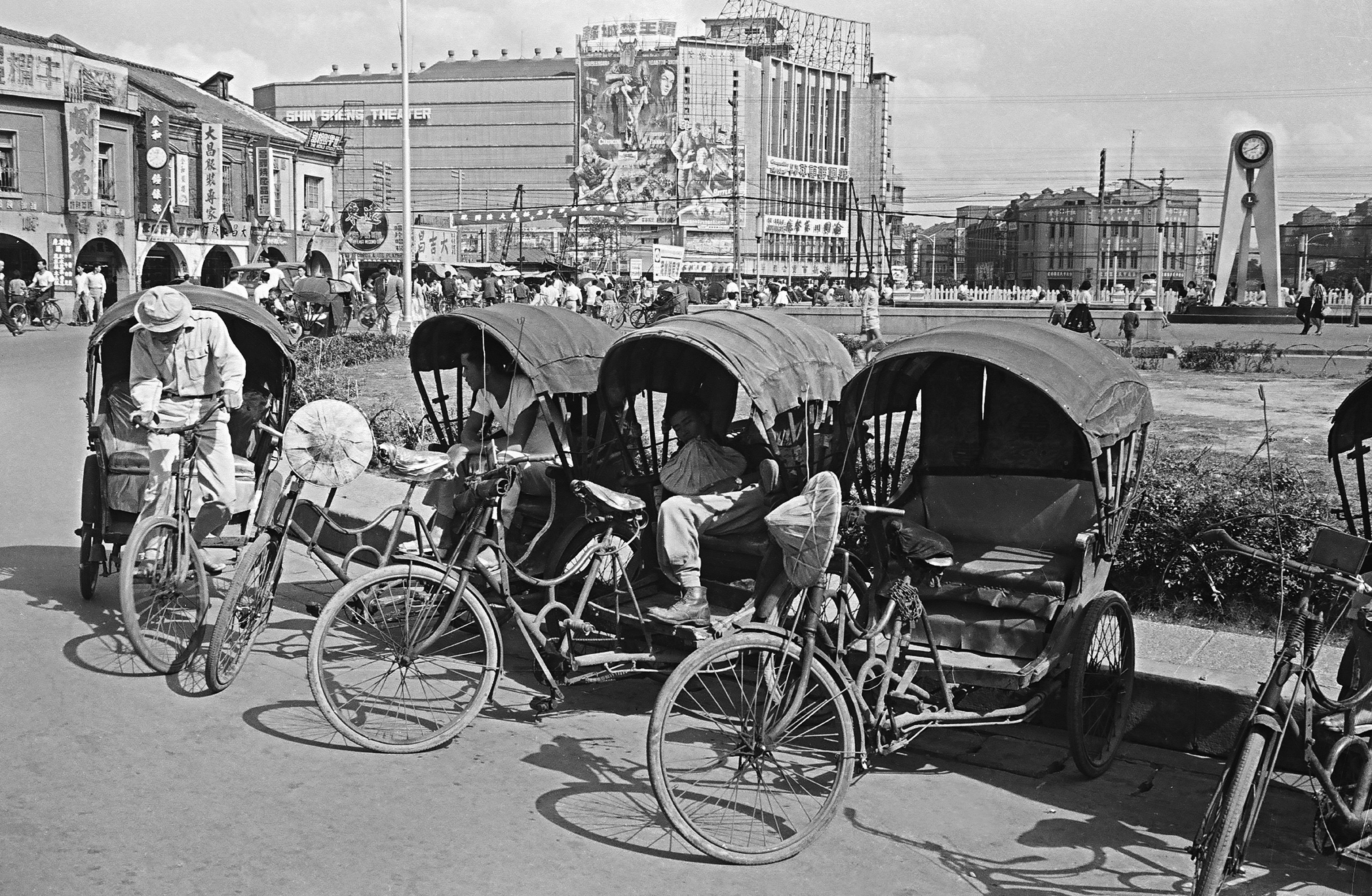 圖中幾輛三輪車正停靠西門圓環旁邊等待客人,背後的大建物則是新生戲院。(另開視窗)