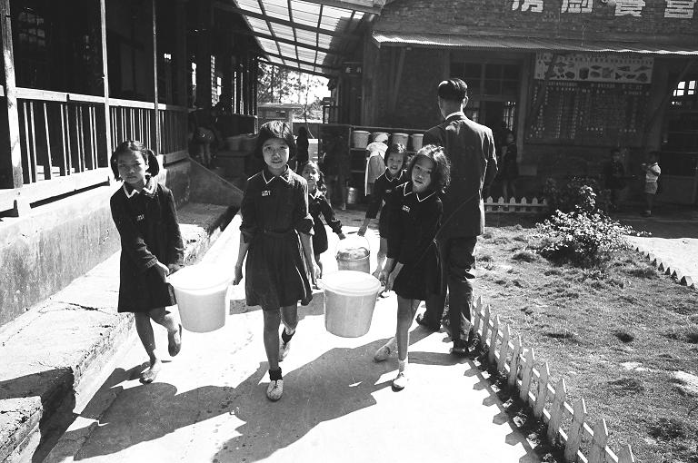 這張照片所拍攝的是學生們一起搬運營養午餐的模樣。營養午餐開始於1959年,臺灣省政府教育廳先在7所國小試辦。(另開新視窗)