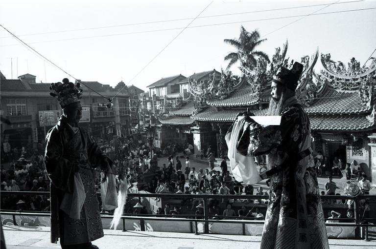 眾多媽祖信徒們群聚在北港朝天宮前的宗聖台下觀看劇團表演酬神戲碼(扮仙戲)。(另開新視窗)