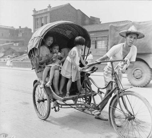 車伕拉著承載大人、小孩的三輪車